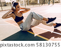 Young beautiful strong girl doing abs exercises 58130755