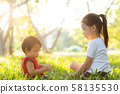 Beautiful young asian kid sitting playing in summer in the park with enjoy and cheerful 58135530