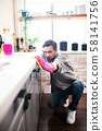 Man wearing jeans and white sneakers cleaning kitchen 58141756