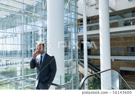 Businessman talking on mobile phone in the corridor 58143600