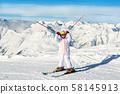 Cute adorable preschooler caucasian kid girl portrait with ski in helmet, goggles and unicorn fun 58145913