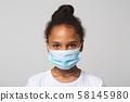 Portrait of little black girl wearing medical mask 58145980