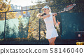 Woman playing tennis on court 58146040
