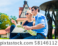 Smiling couple holding map 58146112