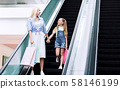 Mother And Little Daughter Standing On Escalator Shopping In Hypermarket 58146199