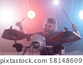 hobby, music and people concept - portrait of a man with white headphones playing drums, having fun 58148609