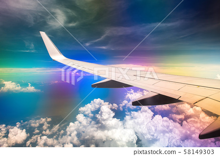 Wing of airplane in cloudy sky with rainbow effect 58149303