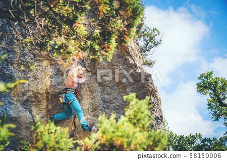 Girl climbing a rock.  58150006