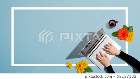 Person using a laptop computer with autumn flowers 58157332