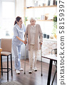 Caregiver assisting woman walking with crutches 58159397