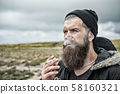 man with beard smoking cigarette at mountain, 58160321