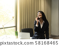 Happy business woman talking on the phone in 58168465