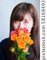 꽃을 가진 젊은 여성 58168493