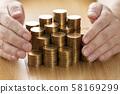 มือที่มีเหรียญทองซ้อนกัน 58169299