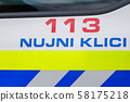 Police sign with emergency dial number on the side of patrol car 58175218