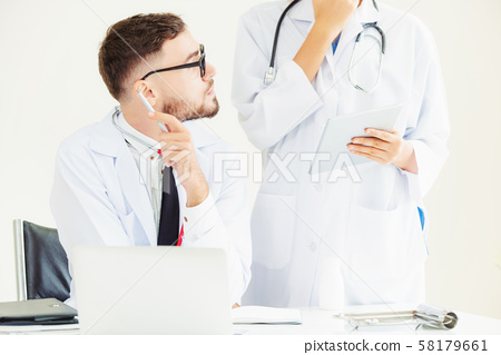 Doctor at hospital works on computer with partner. 58179661