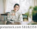 ผู้หญิงที่ดื่มกาแฟในห้อง 58182356