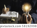 Hand of male holding a light bulb and copy space 58192098