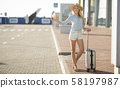 Catch taxi. Young woman standing near airport 58197987