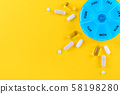different medicines for one week and a pills box on yellow background with copy space 58198280