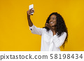 Cheerful black girl holding cellphone and making selfie 58198434