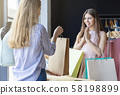 Glad customer looking at gift offering by helpful shop assistant 58198899