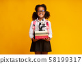 Afro Schoolgirl Holding Microscope And Stack Of Books, Yellow Background 58199317