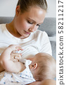 Caring young mother breastfeeds baby girl 58211217
