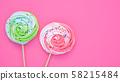 Colorful meringue lollipop on a pink background. 58215484