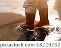 Little girl in red rainboots playing in puddle after rain. Happy fall childhood activity 58220232