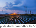 High voltage substation and windmill with strawberry field blue sky at sunset. 58221677