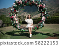 Cute girl having fun on a swing in blossoming garden outdoors on sunny spring day. Spring outdoor activities for kids. 58222153