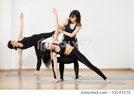 Female team exercising yoga lesson with instructor. Standing yoga poses. Trainer helping doing yoga