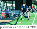 Sporty caucasian man exercising with battle ropes at the gym on green floor. 58247999