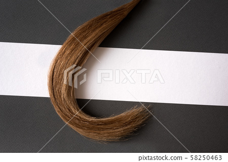 Strand of blonde hair on a black and white 58250463