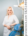 Portrait of female dentist standing at her office 58251464
