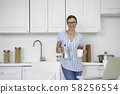 Happy woman with coffee in the kitchen stock photo 58256554