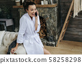 Surprised pretty woman is talking on smartphone 58258298