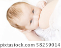 Young woman breastfeeding her little baby boy 58259014