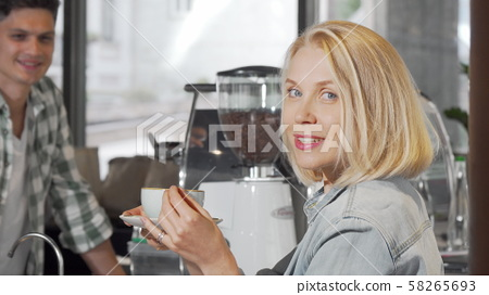 Young woman smiling to the camera after getting a cup of coffee at the coffee shop 58265693
