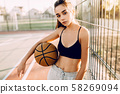 Young sports girl outdoors posing looking at 58269094