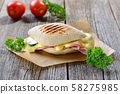 Grilled and pressed panini with ham, melted cheese, cucumber and tomatoes served on a wooden table 58275985