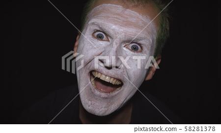 Clown Halloween man portrait. Close-up of an evil clowns face. White face makeup 58281378