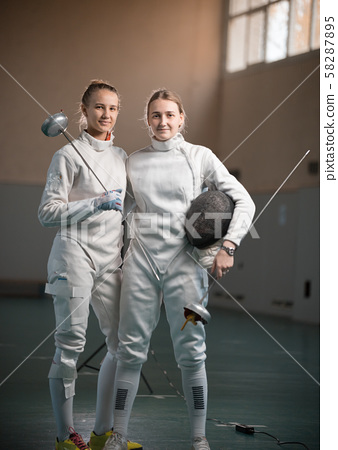 A portrait of two young women fencers standing by each other 58287895