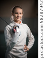 A portrait of a young woman fencer with a singlestick 58287942