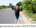 Young Asian boy running on a road 58307096