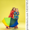 A full length portrait of a bright fashionable girls in a raincoat 58307852