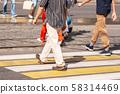 legs of pedestrians walking on the crosswalk 58314469