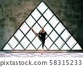 Young beautiful woman doing yoga asana toe pose variation on large triangular window background 58315233