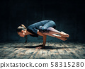 Young attractive woman practicing yoga doing side crane pose in dark room 58315280